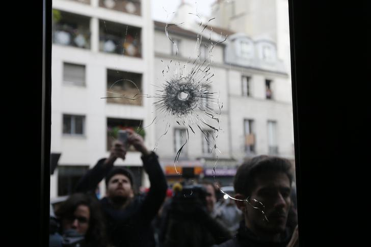 Journalists work outside a restaurant where bullet impacts are seen the day after a series of deadly attacks in Paris, France, November 14, 2015. REUTERS/Gonzalo Fuentes