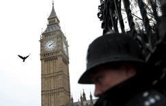 Полицейский охраняет британский парламент в Лондоне. 14 ноября 2015 года. Великобритания увеличит штат разведки на 15 процентов и более чем удвоит расходы на авиационную безопасность для защиты от боевиков-исламистов, планирующих атаки из Сирии, сказал премьер-министр страны Дэвид Кэмерон в понедельник. REUTERS/Suzanne Plunkett