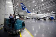 A Bombardier Inc worker takes a photo of the CS300 Aircraft prior to its' test flight in Mirabel February 27, 2015. REUTERS/Christinne Muschi