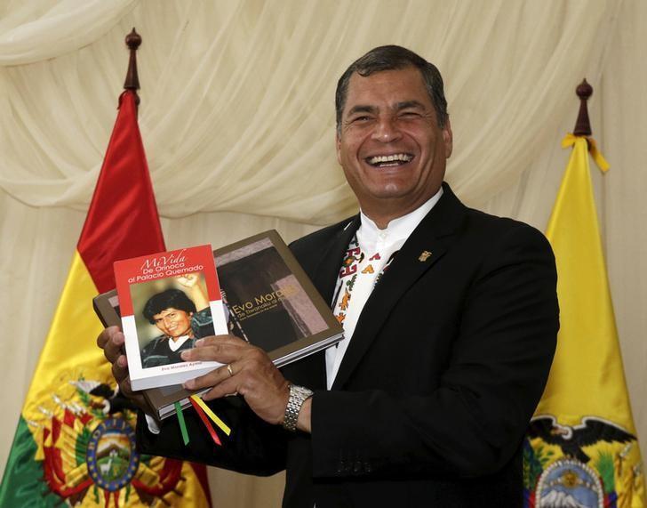 Ecuador's President Rafael Correa holds books about his Bolivian counterpart Evo Morales in Tiquipaya, Bolivia October 12, 2015.  REUTERS/David Mercado