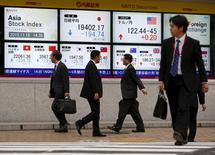 Personas caminan junto a unas pantallas que muestran distintos índices de mercados, afuera de una correduría en Tokio, 16 de noviembre de 2015. Las bolsas de Asia subían el jueves y el dólar cedía por las expectativas de que la Reserva Federal tendrá la confianza suficiente en la economía estadounidense para subir las tasas de interés en diciembre, pero luego procedería con cautela en un mayor ajuste. REUTERS/Thomas Peter