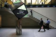 Personas caminan a través del lobby de la Bolsa de Londres, 25 de agosto de 2015. Los metales básicos caían a mínimos en varios años el lunes y el petróleo ampliaba sus pérdidas en medio de una nueva ola de ventas de las materias primas, afectadas por la preocupación sobre la economía de China y el fortalecimiento del dólar. REUTERS/Suzanne Plunkett