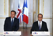 """Президент Франции Франсуа Олланд и премьер-министр Великобритании Дэвид Кэмерон на совместной пресс-конференции в Елийсейском дворце в Париже. 23 ноября 2015 года. Премьер-министр Великобритании Дэвид Кэмерон высказал уверенность в том, что Соединенному Королевству следует наносить авиаудары по позициям """"Исламского государства"""" в Сирии наряду с Францией и другими партнёрами. REUTERS/Eric Gaillard"""
