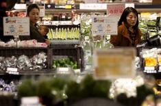 Foto de archivo de personas mirando vegetales en un supermercado en Chiba, al este de Tokio, 26 de febrero de 2014. Japón planea aumentar el salario mínimo e introducir otras medidas para revitalizar a su economía, pero el borrador del proyecto de medidas de estímulo visto el lunes por Reuters aparentemente no contempla nuevas reformas que, según analistas, son necesarias para poner fin a décadas de estancamiento. REUTERS/Yuya Shino/Files