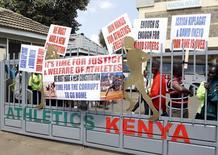 Protesting Kenyan athletes place placards behind closed gates at Riadha House the Athletic Kenya (AK) Headquarters in capital Nairobi November 23, 2015. REUTERS/Noor Khamis