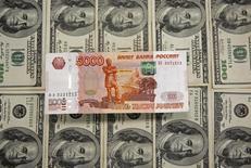 Рублевые и долларовые банкноты. Сараево, 9 марта 2015 года. Рубль растет утром вторника на фоне дорожающей нефти и перед завтрашними крупными налогами, против него по-прежнему нежелание Запада смягчать санкции против России в обмен на совместную борьбу с терроризмом. REUTERS/Dado Ruvic