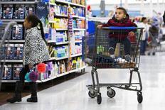 Una niña se aleja de un niño en un carrito de compras, mientras su familia miran productos en una tienda Walmart en Secaucus, Nueva Jersey, 11 de noviembre de 2015. El gasto del consumidor estadounidense subió levemente en octubre debido a que los hogares aprovecharon el aumento de los salarios para incrementar sus ahorros a los niveles más altos en casi tres años, lo que apunta a un crecimiento económico moderado en el cuarto trimestre. REUTERS/Lucas Jackson