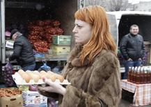 Женщина на рынке в Ставрополе. 7 марта 2015 года. Инфляция в России вторую неделю держится у отметки 0,1 процента, снизившись в годовом исчислении до 15,1 процента, которые в январе 2016 года могут обернуться однозначным значением. REUTERS/Eduard Korniyenko