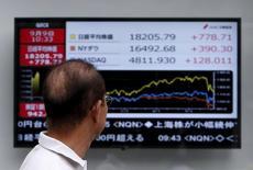 Un peatón mira un tablero electrónico que muestra la reciente fluctuación del índice Nikkei, afuera de una correduría en Tokio, Japón, 9 de septiembre de 2015. Las acciones japonesas cayeron el viernes en un débil volumen de negocios en momentos en que los indicadores técnicos sugieren que el mercado está sobrecomprado y vulnerable a una corrección. REUTERS/Yuya Shino