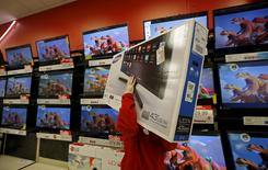 A worker carries a television for a customer who made a purchase during Black Friday Shopping at a Target store in Chicago, Illinois, United States, November 27, 2015. REUTERS/Jim Young