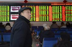 An investor looks on in front of an electronic board showing stock information at a brokerage house in Fuyang, Anhui province, China, November 27, 2015.  REUTERS/China Daily
