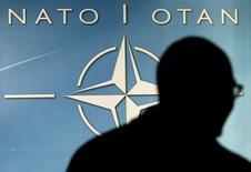 Мужчина на фоне логотипа НАТО. Брюссель, 1 декабря 2003 года.  Страны-члены НАТО расходятся во взглядах относительно того, какой сигнал следует дать Грузии о перспективе её присоединения к военному блоку, говорят дипломаты. По мнению некоторых европейских участников альянса, НАТО будет не в состоянии защитить бывшую советскую республику в случае конфликта с Россией. REUTERS/Thierry Roge