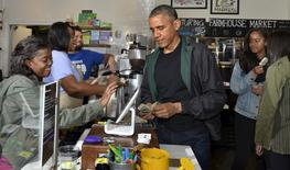 U.S. President Barack Obama (C) pays for purchases at Pleasant Pops, as daughters Malia and Sasha enjoy a popsicle, in Washington, November 28, 2015.  REUTERS/Mike Theiler
