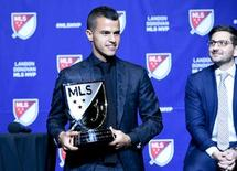 Dec 2, 2015; Toronto, Ontario, Canada;  Toronto FC midfielder Sebastian Giovinco holds the Landon Donovan MVP trophy after being named 2015 most valuable player by Major League Soccer during a presentation at Air Canada Centre. Looking on at right is Toronto FC general manager Tim Bezbatchenko.  Mandatory Credit: Dan Hamilton-USA TODAY Sports