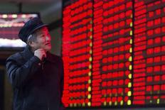 Un inversor mira un tablero electrónico que muestra la información de las acciones en una correduría en Nanjing, China, 3 de diciembre de 2015. Las acciones chinas subieron por cuarto día consecutivo el jueves, recuperando la mayor parte de la pérdida de un 5 por ciento del viernes pasado, luego de que los principales valores ligados a los bancos y al sector de propiedades apoyaron a los principales índices del país. REUTERS/China Daily