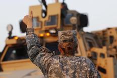 """Американская военнослужащая разрешает проезд конвою на границе Кувейта и Ирака. 18 декабря 2011 года. Президент США Барак Обама сказал, что его решение отправить дополнительную группу спецназа для борьбы с """"Исламским государством"""" в Ираке не означает подготовку к новой масштабной военной кампании, вылившейся в затяжной кровопролитный конфликт. REUTERS/Shannon Stapleton"""