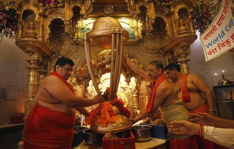 Hindu priests hold a replica of the Cricket World Cup trophy during a ''puja'', or blessing ceremony, at the Siddhivinayak temple in Mumbai February 17, 2011. REUTERS/Danish Siddiqui/Files