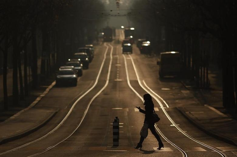A woman crosses a street while using a mobile phone in Bern March 4, 2011. REUTERS/Michael Buholzer