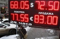 Мужчина у пункта обмена валюты в Москве. 30 января 2015 года. Рубль обновил локальные минимумы к доллару и евро при открытии торгов вторника, но в целом изменения незначительны на фоне стабилизации нефти вблизи многолетних минимумов - от колебаний нефтяных котировок будет зависеть дальнейшая динамика рубля. REUTERS/Grigory Dukor