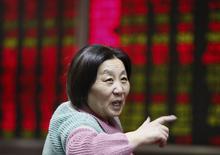 Una inversora habla con otros frente a un tablero electrónico que muestra información bursátil, en una correduría en Pekín, China, 7 de diciembre de 2015. Las acciones chinas subieron el miércoles, luego de que los valores ligados al sector inmobiliario se fortalecieron por las expectativas de medidas oficiales de apoyo. REUTERS/Stringer