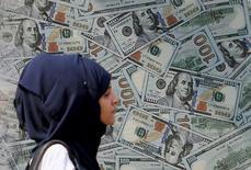 Женщина проходит мимо пункта обмена валюты в Каире 19 ноября 2015 года. Американский доллар стремился отыграть утраченные позиции в четверг после больших потерь в результате закрытия инвесторами длинных позиций; австралийский доллар резко вырос, после того как неожиданные данные об увеличении занятости застали инвесторов врасплох. REUTERS/Mohamed Abd El Ghany