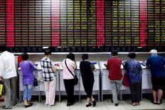 Inversores miran pantallas de computadores que muestra la información de las acciones, en una correduría en Shanghái, China, 8 de julio de 2015. Las acciones chinas cerraron a la baja el jueves, cediendo unas ganancias modestas, incluso después de que los reguladores tranquilizaron a los inversores de que las reformas a las Ofertas Públicas Iniciales (OPIs) no dará paso a una gran cantidad de ofertas simultáneas. REUTERS/Aly Song/Files
