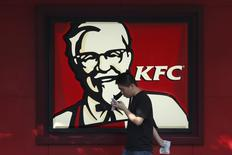 A man walks past a logo of KFC, outside a restaurant in Shanghai, China, July 30, 2015.  REUTERS/Aly Song