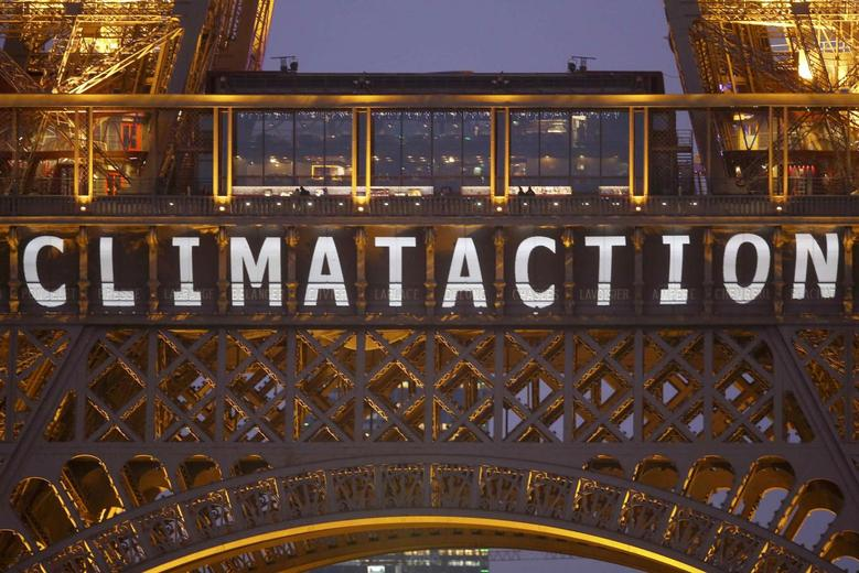 The slogan ''Climate action'' is projected on the Eiffel Tower as part of the World Climate Change Conference 2015 in Paris, December 11, 2015.   REUTERS/Charles Platiau