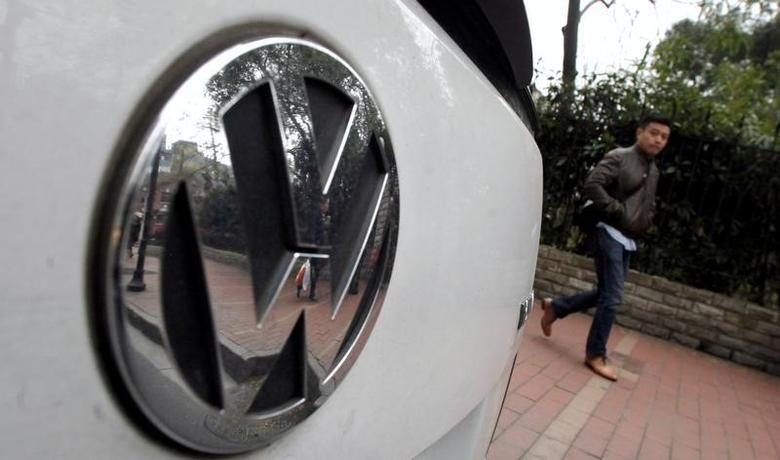 A man walks past a Volkswagen Touran along a busy street in downtown Shanghai in this March 20, 2013 file photo. REUTERS/Carlos Barria