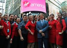 Virgin America Inc. President and Chief Executive Officer David Cush (3rd R) poses for photographs with Virgin America flight crews at the NASDAQ Market Site in New York, November 14, 2014. REUTERS/Mike Segar