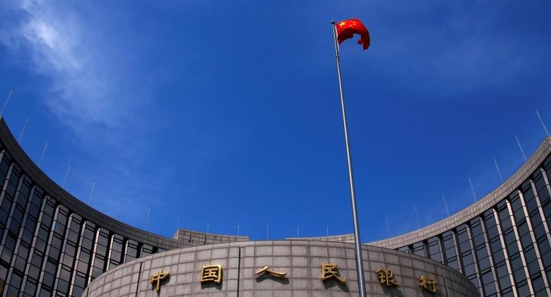 A Chinese national flag flutters in front of the headquarters of the People's Bank of China, China's central bank, in central Beijing, May 16, 2014. REUTERS/Petar Kujundzic