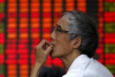Un inversor mira un tablero electrónico que muestra la información de las acciones, en una correduría en Shanghái, 10 de julio de 2015. Las acciones chinas cerraron estables el miércoles a pesar de un salto de los valores energéticos, luego de que los papeles de las principales firmas inmobiliarias se desplomaron y la mayoría de los otros sectores se debilitó antes de una subida prevista de las tasas de interés en Estados Unidos. REUTERS/Aly Song