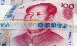 Foto de archivo de un billete de 100 yuanes en un banco en Seúl, 10 de noviembre de 2010. El banco central de China está en guardia ante la posibilidad de un ataque repentino contra el yuan en los mercados extranjeros y está listo para intervenir si la brecha entre las tasas de cambio dentro y fuera del país se vuelve una fuente de desestabilización, dijeron fuentes involucradas en las discusiones de política. REUTERS/Lee Jae-won/Files