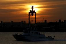 Un barco frente a una grúa en un puerto en Tokio, Japón, 7 de diciembre de 2015. El Gobierno de Japón se encamina a elevar su pronóstico de crecimiento económico para el próximo año fiscal, pero algunos economistas creen que las cifras se basan en unas expectativas poco realistas de aumentos salariales. REUTERS/Yuya Shino