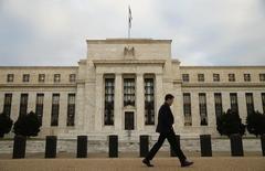 Ocho años después de que una devastadora recesión abrió una era de política monetaria ultraexpansiva en Estados Unidos, la Reserva Federal parecía lista el miércoles para subir las tasas de interés por vez primera desde 2006, en una señal de que la mayor economía mundial superó la mayoría de las heridas causadas por la crisis financiera global.. En la foro, un hombre camina junto a la sede de la Reserva Federal en Washington, el 16 de diciembre de 2015.  REUTERS/Kevin Lamarque