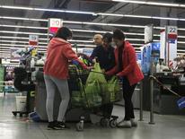 Unas personas realizando sus compras en un supermercado en Buenos Aires, ago 1, 2014. El levantamiento de restricciones en el mercado argentino de divisas y la devaluación del peso local dispararán una mayor inflación, que golpeará al consumo y hará que la economía termine el año próximo estancada o en una leve recesión para repuntar recién en 2017, dijeron analistas.  REUTERS/Enrique Marcarian