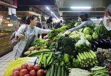 Una clienta compra vegetales en un mercado en Qingdao, China, 14 de octubre de 2015. Las ventas minoristas de China, una medida clave del consumo interno en la segunda economía más grande del mundo, probablemente registrarán un crecimiento más lento este año en comparación con el 2014, informó el Ministerio de Comercio. REUTERS/Stringer