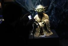 "A visitor takes a picture of character Yoda from the Star Wars film series during a press preview for the exhibit ""Star Wars Identities"" at the MAK museum in Vienna, Austria, December 17, 2015.  REUTERS/Leonhard Foeger"