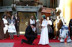 Andrew Porters kneels in front of Caroline Ritter from Australia during their wedding ceremony accompanied by people dressed as characters from Star Wars in the forecourt of the TCL Chinese Theatre in Hollywood, California December 17, 2015.    REUTERS/Mario Anzuoni