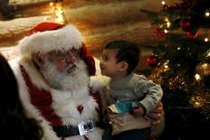 Two-year-old Elijah Pham presents his wishes to actor John Field, dressed as Santa Claus, at a Christmas grotto at the Wetland Centre in London, Britain, December 5, 2015. REUTERS/Stefan Wermuth