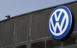A worker wearing a protective mask stands next to a Volkswagen logo at a dealership in Madrid, Spain, December 16, 2015.  REUTERS/Sergio Perez