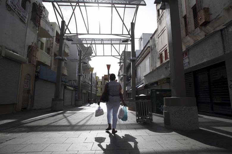 A woman carries bags while walking in a commercial area with stores either closed or offered for sale in San Juan, Puerto Rico, July 31, 2015. REUTERS/Alvin Baez