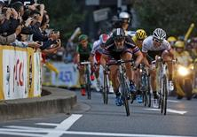Giant-Alpecin rider John Degenkolb (3rd R) of Germany and Trek Factory rider Fumiyuki Beppu (R) of Japan sprint to the finish line as spectators take pictures of them during the Tour de France Saitama Criterium cycling race in Saitama, north of Tokyo, Japan, October 24, 2015. REUTERS/Yuya Shino