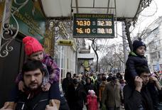 Люди у пункта обмена валюты в Краснодаре. 19 декабря 2015 года. Рубль начал торги среды ростом на фоне повышения цен на нефть Brent, упавших накануне к минимальным за почти 11,5 лет уровням, на стороне рубля экспортные продажи под уплату налогов, а также низкий физический спрос на валюту со стороны корпораций и банков для погашения внешнего долга. REUTERS/Eduard Korniyenko