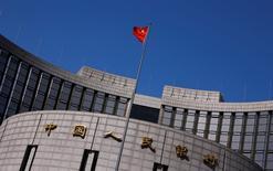Una bandera china ondea afuera de la sede del Banco Central de China, en Pekín, 3 de abril de 2014. El Banco Popular de China (BPC) dijo el miércoles que ampliará las horas de negociación del yuan en el mercado de divisas con sede en Shanghái desde el 4 de enero del 2016. REUTERS/Petar Kujundzic