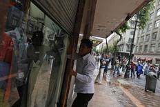 Un empleado baja la cortina de una tienda durante una manifestación por el Día del Trabajador en Ciudad de México, mayo 1, 2014. Las exportaciones de México cayeron en noviembre tras dos meses consecutivos al alza, en tanto que la tasa de desempleo se moderó a su menor nivel desde octubre del 2008, según datos oficiales divulgados el jueves.  REUTERS/Tomas Bravo