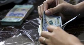 Un empleado contando billetes en un banco vietnamita en Hanoi, ago 12, 2015. El dólar se depreciaba el jueves contra una cesta de monedas y se encaminaba a registrar su retroceso más significativo desde abril, debido a que los operadores reanudaron una toma de ganancias a la espera de que la moneda estadounidense repunte más adelante por el panorama sobre las tasas de interés.  REUTERS/Kham