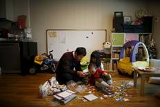 Chung Sang-hoon talks to his daughter and son at their apartment in Seoul, South Korea, December 14, 2015. REUTERS/Kim Hong-Ji