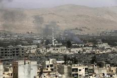 """Дым поднимается над пригородом Дамаска 14 сентября 2015 года. Захран Аллуш, лидер """"Джаиш аль-Ислам"""", одной из наиболее мощных повстанческих группировок в Сирии, был убит в результате авиаудара в пригороде Дамаска, сообщили два источника из числа повстанцев и сирийское государственное ТВ в пятницу. REUTERS/Bassam Khabieh"""