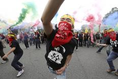 "People throw smoke grenades during the annual Labour Day protest in front of Presidential Office in Taipei, Taiwan, in this May 1, 2015 file picture. The head banner reads, ""shorten working hours; no overfatigue."" REUTERS/Patrick Lin"
